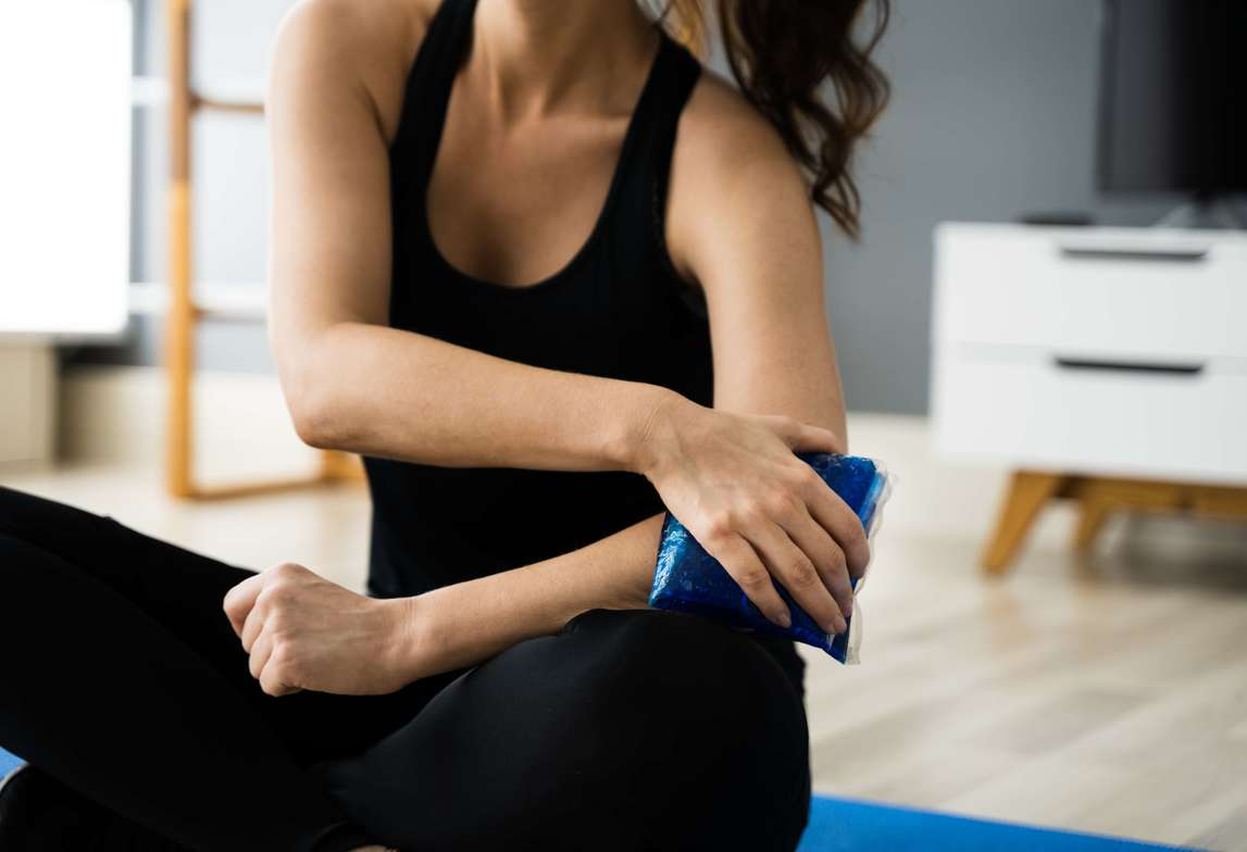 Woman in black using an ice pack on her arm due to pain while performing yoga
